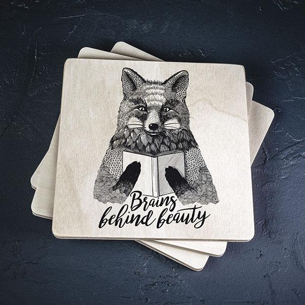 """Balts krūžu paliktnis ar melnu lapsaszīmējumu un tekstu: """"Brains behind beauty"""""""