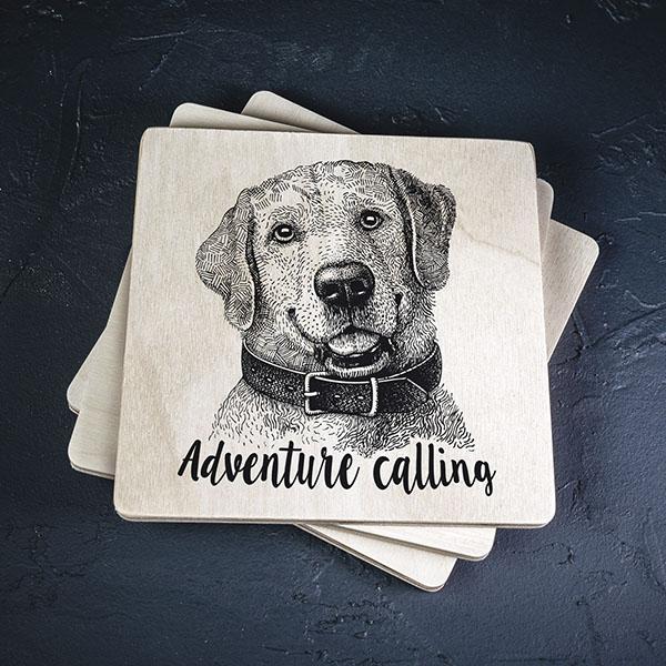 """Balts krūžu paliktnis ar melnu suņa zīmējumu un tekstu: """"Adventure calling"""""""