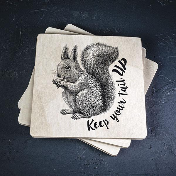 """Balts krūžu paliktnis ar melnu vāveres zīmējumu un tekstu: """"Keep your tail up"""""""