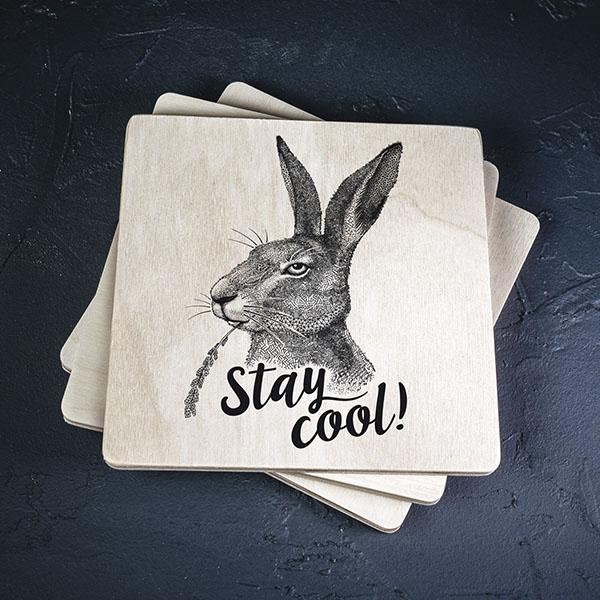 """Balts krūžu paliktnis ar melnu zaķa zīmējumu un tekstu: 'Stay cool!"""""""