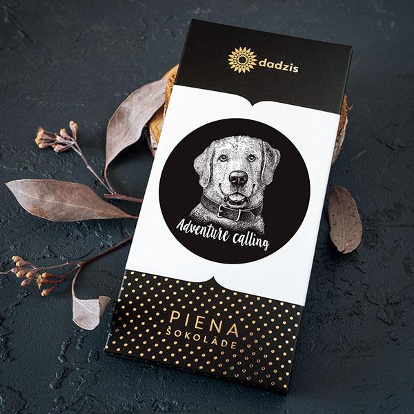 """Piena šokolāde ar iepakojumu, uz kura ir suņa zīmējums un teksts: """"Adventure calling"""""""