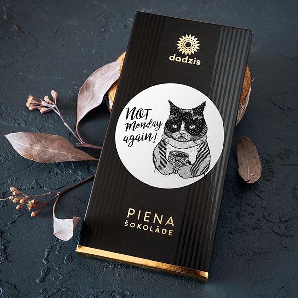 """Piena šokolāde ar iepakojumu, uz kura ir kaķa zīmējums un teksts: """"Not Monday again!"""""""