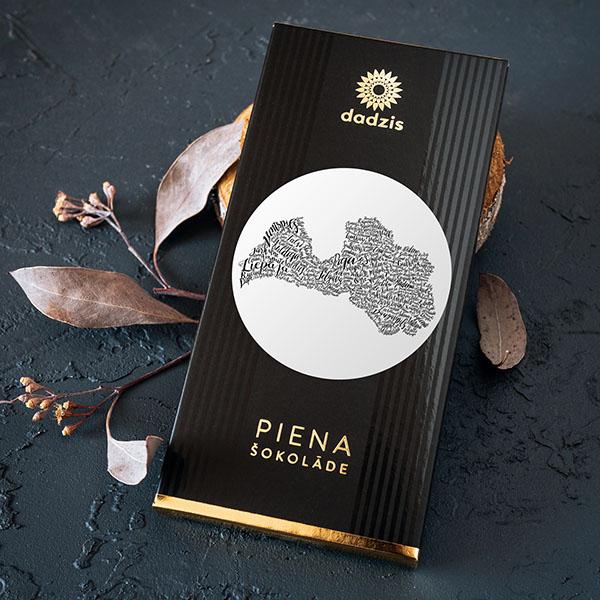 Piena šokolāde ar iepakojumu, uz kura ir Latvijas kontūra un pilsētu zīmējums.