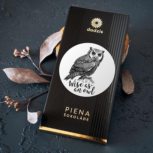 """Piena šokolāde ar iepakojumu, uz kura ir pūces zīmējums un teksts: """"Wise as an owl"""""""