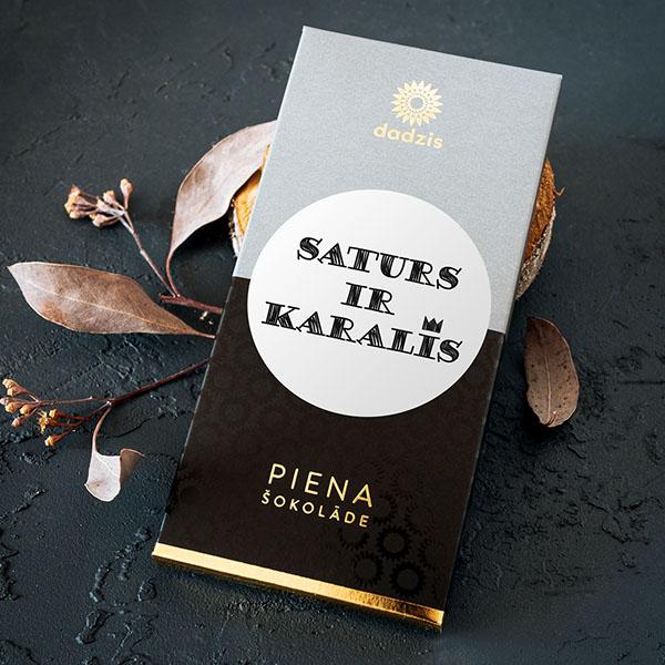 """Piena šokolāde ar iepakojumu, uz kura ir teksts: """"Saturs ir karalis"""""""