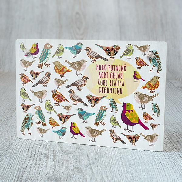 """Dekoratīvais dēlītis ar krāsainu putnu zīmējumu un tekstu: """"Kurš putniņš agri ceļas, agri slauka deguntiņu"""""""