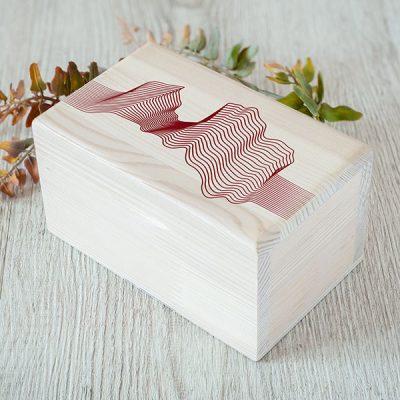 Balta koka kaste ar sarkanu Latvijas kartes kontūru līniju drukā. Kastei ir 1x2 nodalījumi