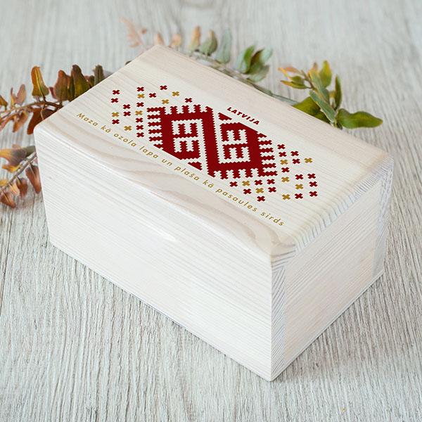 """Balta kokakaste ar saranu Latvijas ornamentu un tekstu: """"Mazakā ozola lapa, plaša kā pasaules sirds"""". Kastei ir 1x2 nodalījumi."""