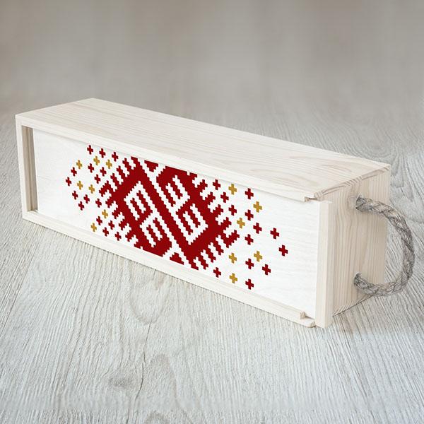 Balta koka kaste vīna pudelei ar krāsainu Latijas ornamentu.