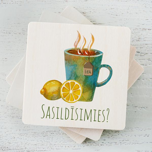 """Balts magnēts ar krāsainu tējas tases zīmējumu un tekstu: """"Sasildīsimies?"""""""