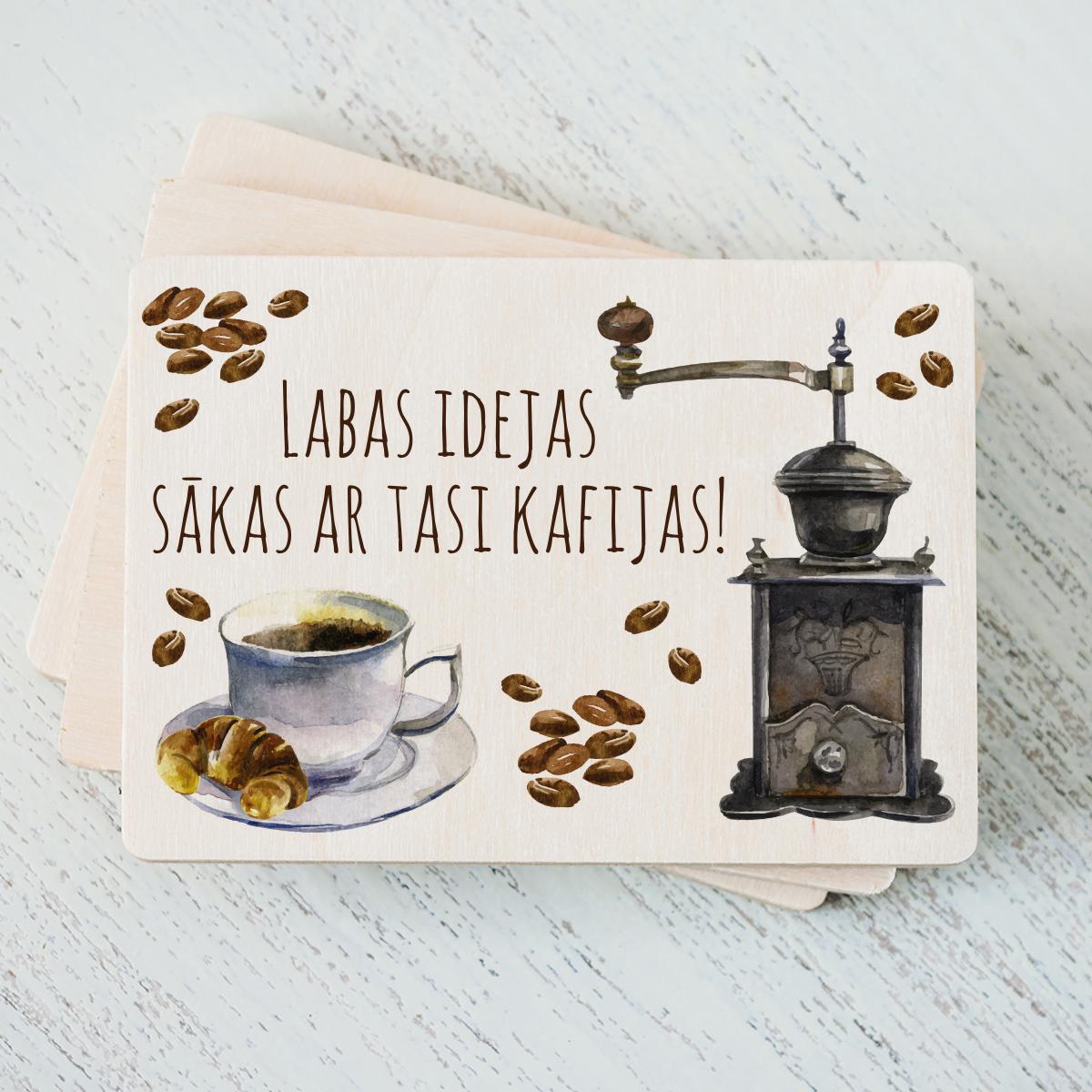 """Balts magnēts ar krāsainu kafijas tases zīmējumu un tekstu: """"Labas idejas sākas ar tasi kafijas!"""""""
