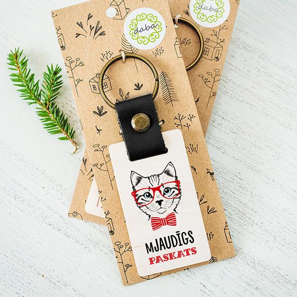 """Koka atslēgu piekariņš ar kaķa un briļļu zīmējumu un tekstu: """"Mjaudīgs paskats"""""""