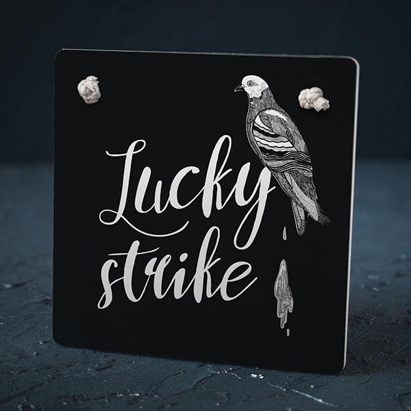 """Melns dekoratīvais koka dēlītis ar baltu baloža zīmējumu un tekstu: """"Lucky strike"""""""