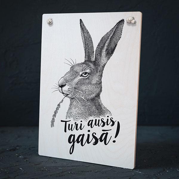 """Balts dekoratīvais dēlītis ar melnu zaķa zīmējumu un tekstu: """"Turi ausis gaisā!"""""""
