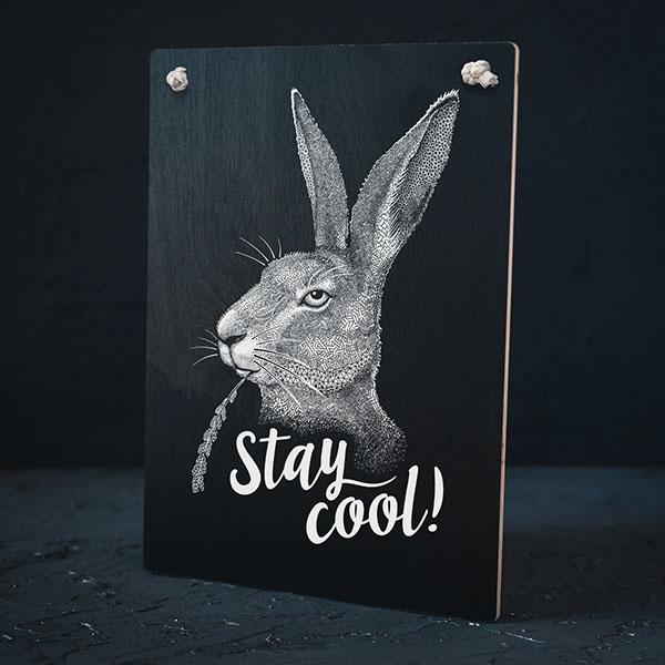 """Melns dekoratīvais koka dēlītis ar baltu zaķa zīmējumu un tekstu: """"Stay cool!"""""""