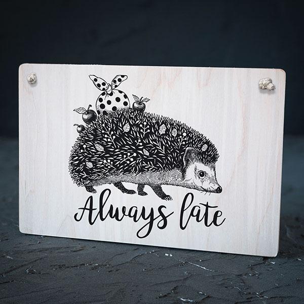 """Balts dekoratīvais koka dēlītis ar melnu eža zīmējumu un tekstu: """"Always late"""""""