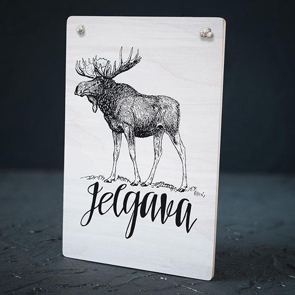 """Balts dekoratīvais koka dēlītis ar melnu aļņa zīmējumu un tekstu: """"Jelgava"""""""