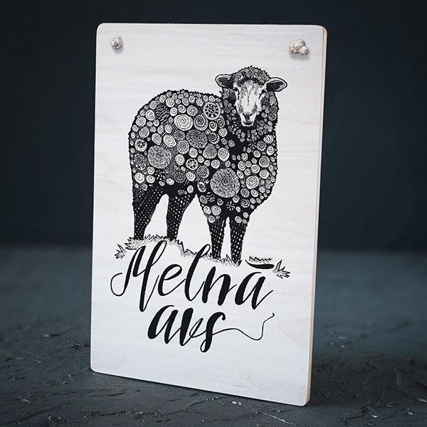"""Balts dekoratīvais koka dēlītis ar melnu aitas zīmējumu un tekstu: """"Melnā avs"""""""