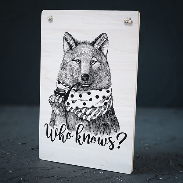 """Balts dekoratīvais koka dēlītis ar melnu vilka zīmējumu un tekstu: """"Who knows?"""""""
