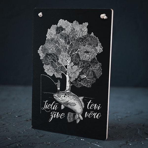 """Melns dekoratīvais koka dēlītis ar baltu zivs zīmējumu un tekstu: """"Lielā zive tevi vēro"""""""
