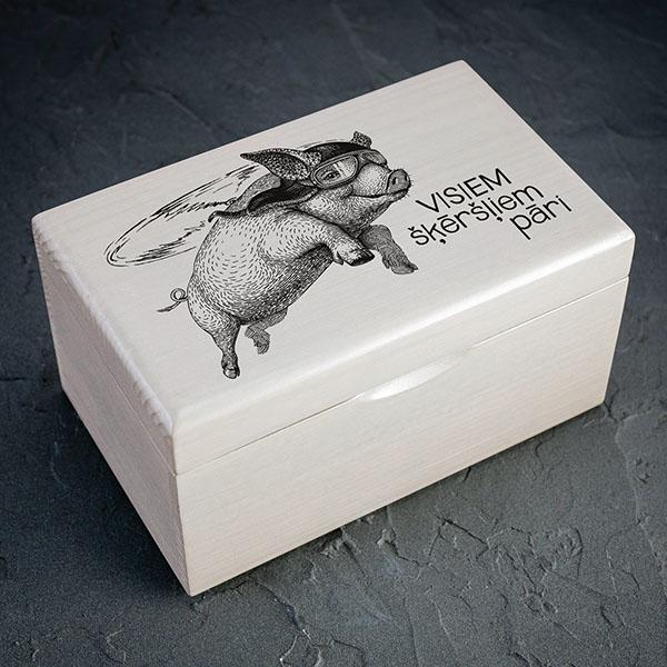 """Balta koka kaste ar melnu cūkas zīmējumu un tekstu: """"Visiem šķēršļiem pāri"""". Kastei ir 1x2 nodalījumi."""