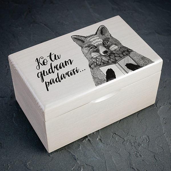"""Balta koka kaste ar melnu lapsas zīmējumu un tekstu: """"Ko tu gudram padarīsi..."""". Kastei ir 1x2 nodalījumi."""