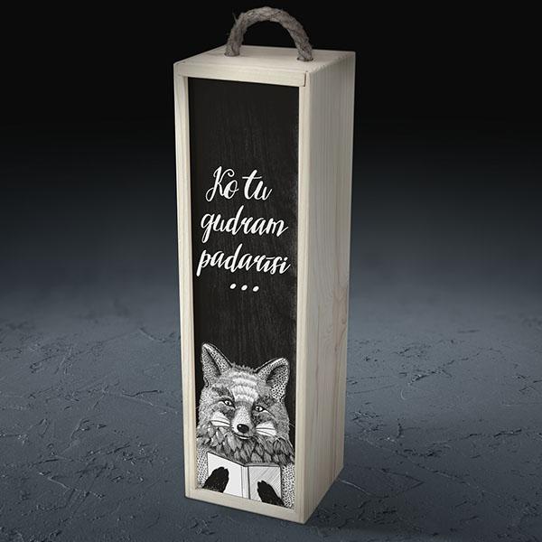 """Balta koka kaste vīna pudelei ar lapsas zīmējumu un tekstu: """"Ko tu gudram padarīsi..."""""""