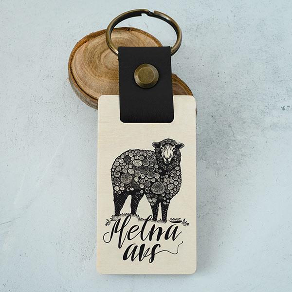 """Koka atslēgu piekariņš ar aitas zīmējumu un tekstu: """"Melnā avs"""""""