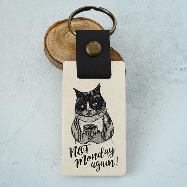 """Koka atslēgu piekariņš ar kaķa zīmējumu un tekstu: """"Not Monday again!"""""""