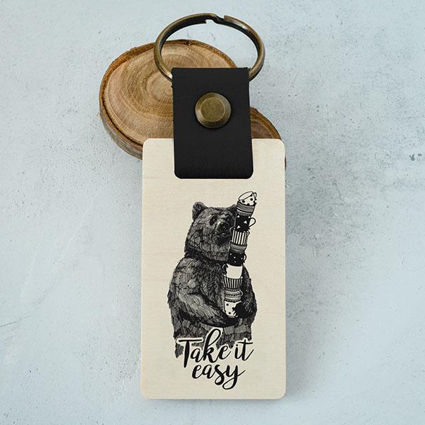 """Koka atslēgu piekariņš ar lāča zīmējumu un tekstu: """"Take it easy"""""""