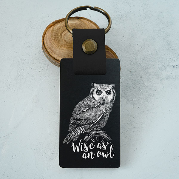 """Koka atslēgu piekariņš ar pūces zīmējumu un tekstu: """"Wise as an owl"""""""