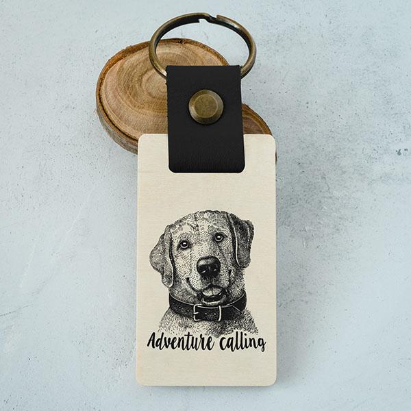 """Koka atslēgu piekariņš ar suņa zīmējumu un tekstu: """"Adventure calling"""""""