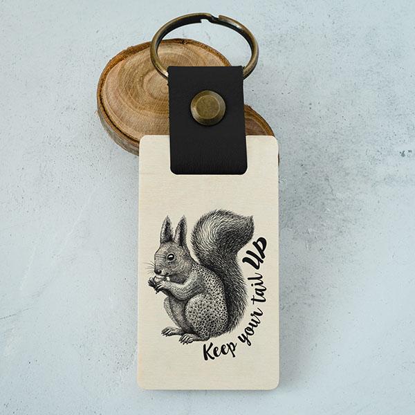 """Koka atslēgu piekariņš ar vāveres zīmējumu un tekstu: """"Keep your tail up"""""""