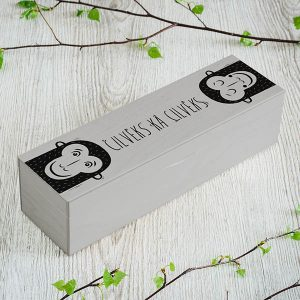 """Pelēka koka kaste ar 1x4 nodalījumiem un mērkaķu zīmējumu un tekstu: """"Cilvēks kā cilvēks"""""""