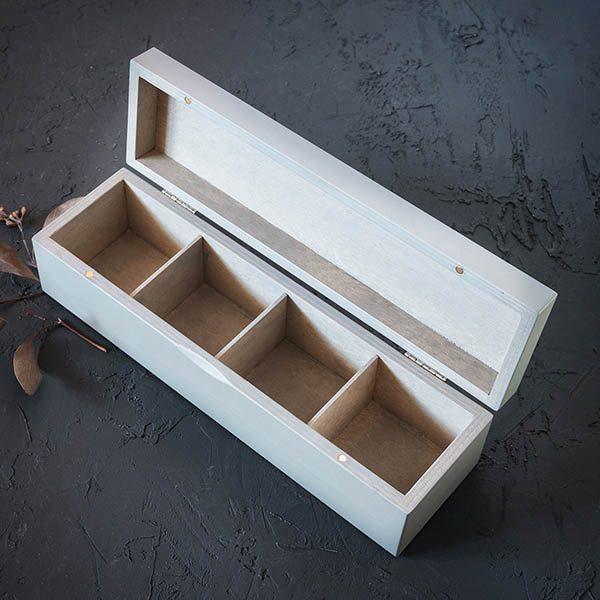 Atvērta, pelēka koka kaste ar 1x4 nodalījumiem.
