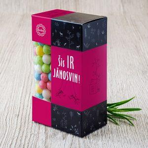 """Dražejas krāsainā kastītē ar tekstu: """"Šis ir jānosvin"""""""