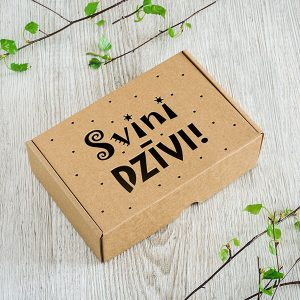 "Kartona kaste ar lāzergravētu tekstu: ""Svini dzīvi!"""