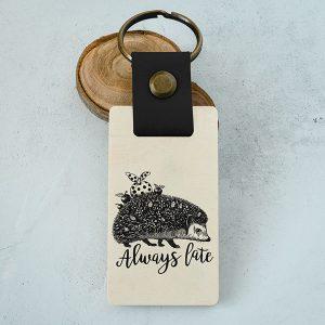 """Koka atslēgu piekariņš ar eža zīmējumu un tekstu: """"Always late"""""""
