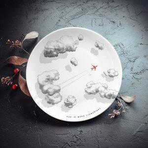 """Mazais šķīvis ar melniem mākoņiem un sarkanas lidmašīnas zīmējumu un tekstu: """"Kur ir mana lidmašīna?"""""""