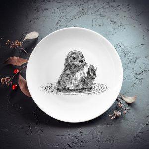 Mazais šķīvis ar melnu roņa zīmējumu.