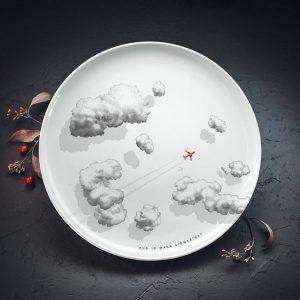"""Lielais šķīvis ar melniem mākoņiem un sarkanas lidmašīnas zīmējumu un tekstu: """"Kur ir mana lidmašīna?"""""""