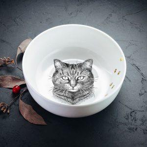 Vidēji mazā bļodiņa ar melnu mājas kaķa zīmējumu un zelta elementu.