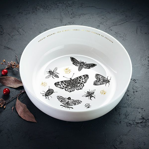 """Balta vidēji lielā bļoda ar melnu un zelta kukaiņu zīmējumu un tekstu: """"Kukaini ragaini tev grezni svārki, ne tādi kungam, ne ķēniņam"""""""