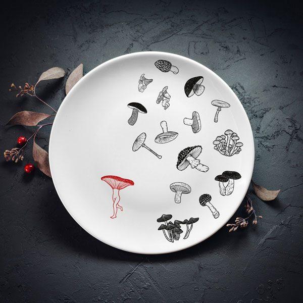 Vidējais šķīvis ar melnu sēņu zīmējumu un sarkanu elementu.
