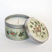 svece metāla traukā ar greipfrūta un vaniļas smaržu un attēlotu briedi ar ziemas briedi