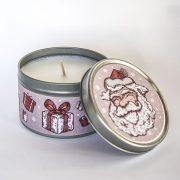svece metāla traukā ar greipfrūta un vaniļas smaržu un attēlotu salaveci un dāvanām